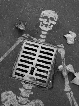 Cool idea turning a street drain grate into a skeleton ribcage!